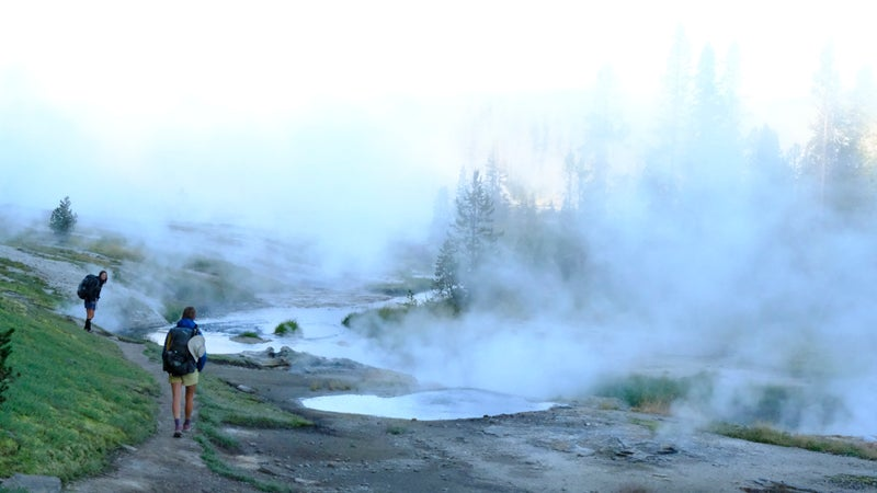 Monica and Aiden in Yellowstone National Park, walking a geyser basin in the early morning