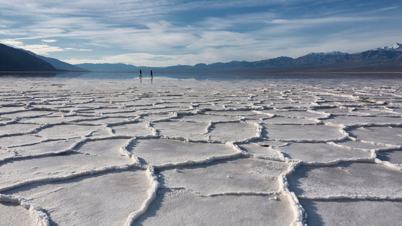 Badwater salt polygons in morning light with silhouette two people
