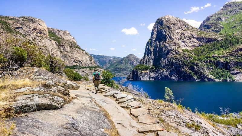 Hiking on the shoreline of Hetch Hetchy reservoir in Yosemite National Park, Sierra Nevada mountains, California; the reservoir is one of the main sources of drinking water for the San Francisco bay