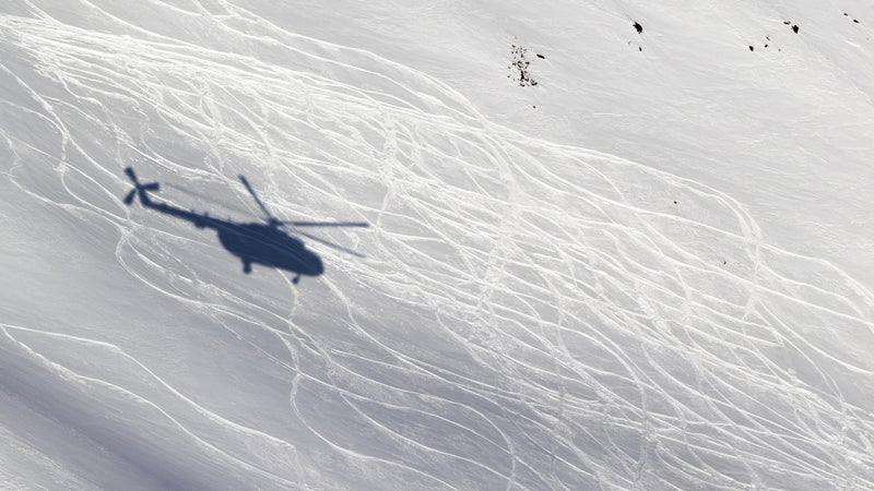 Shadow from helicopter on snowy off-piste ski slope