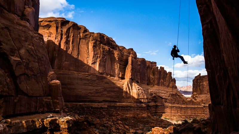 Free-hanging Rappel into Arches National Park canyon in Southern Utah desert.