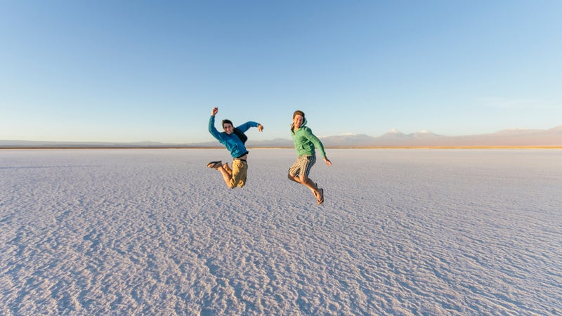 Two Male Friends Jumping Happy On Salt Flat Desert Landscape While Adventure Travel