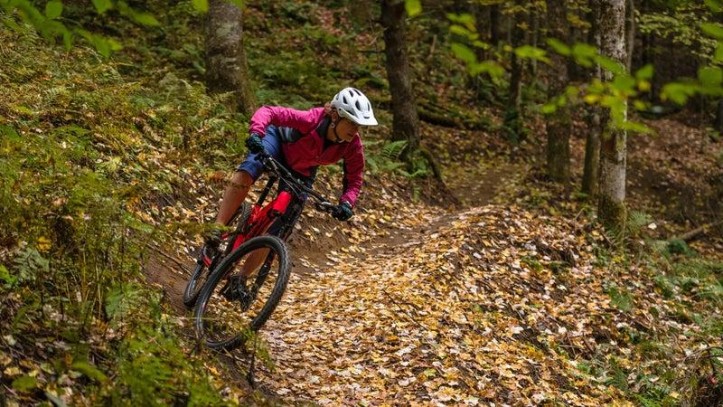 Woman mountain biker corners through autumn leaves
