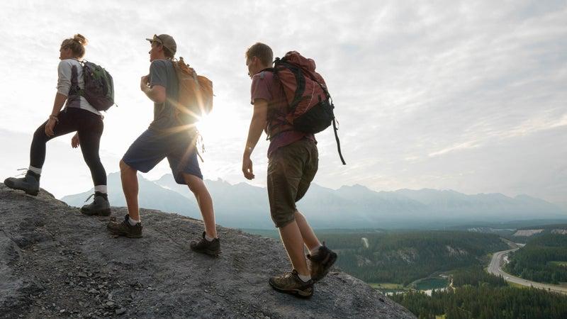 Hikers climb ridge above sunrise, valley