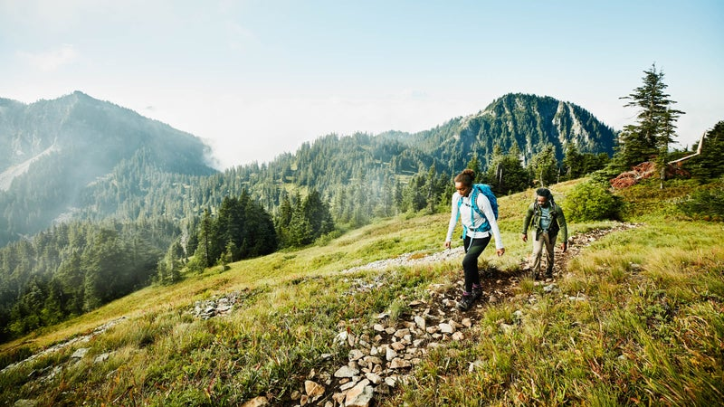 Daughter leading father on morning hike up mountainside