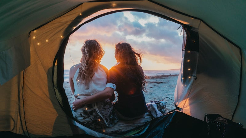 Young adult couple admiring the sunset in a tent on the beach
