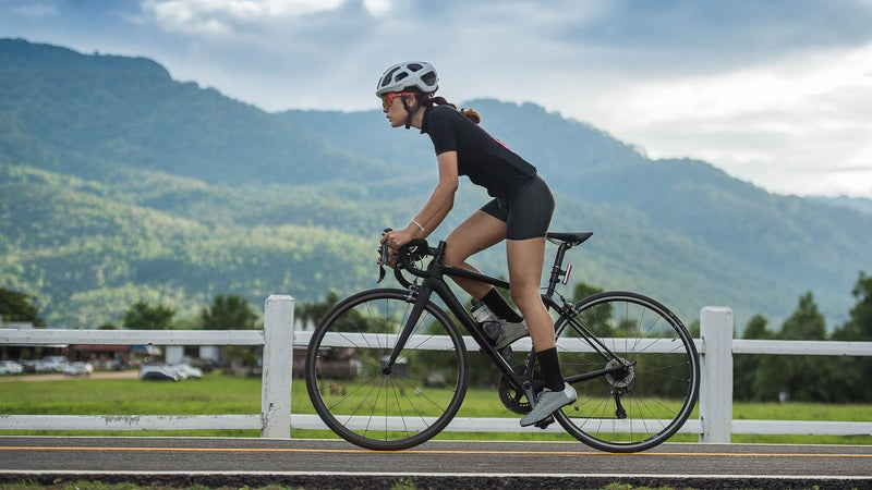 Asian female cyclist cycling on track