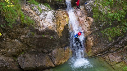 Canyoning in a narrow gorge filled with rapids, pools and waterfalls in the Soca valley near Bovec, Slovenia.