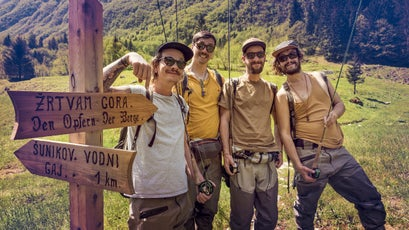 Slovenia, Bovec, four anglers posing at signpost on meadow near Soca river