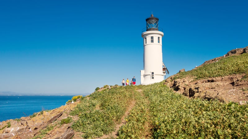 People hike at lighthouse on Anacapa Island in Channel Islands National Park California