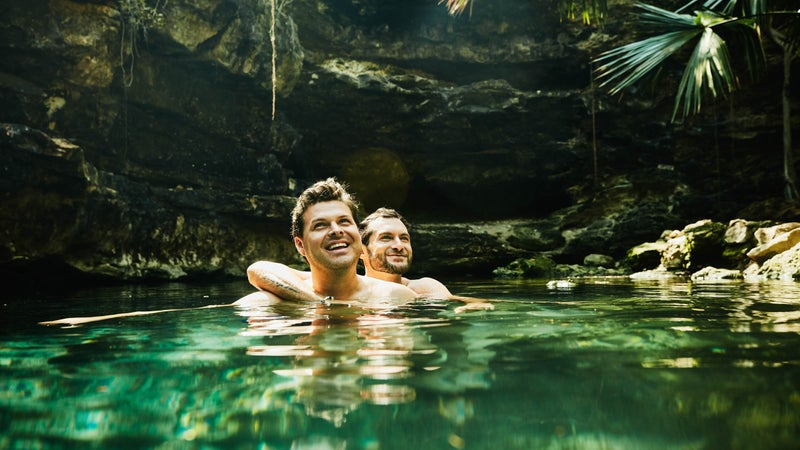 Smiling gay couple embracing while swimming in cenote during vacation