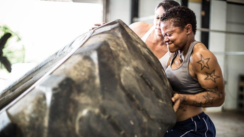 women doing tire-flip exercise