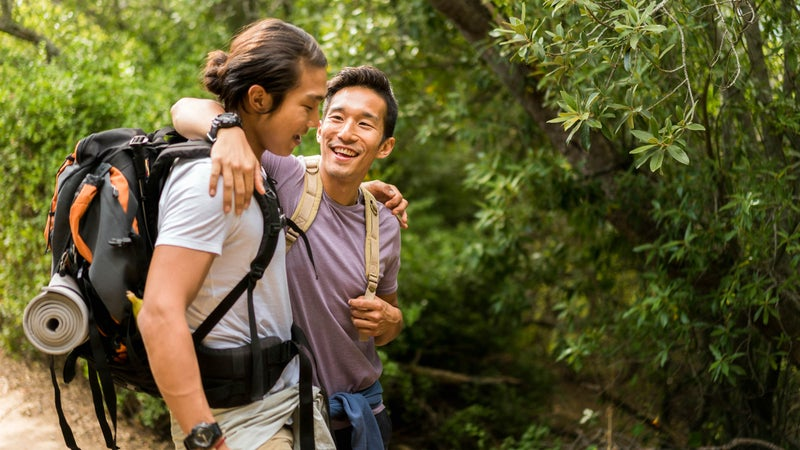 Happy friends talking while hiking in forest