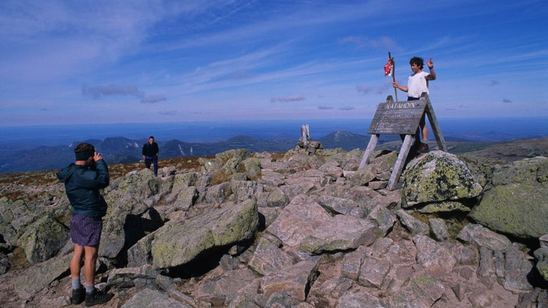 Hikers celebrating at the northern terminus of the Appalachian Trail atop Katahdin in Maine