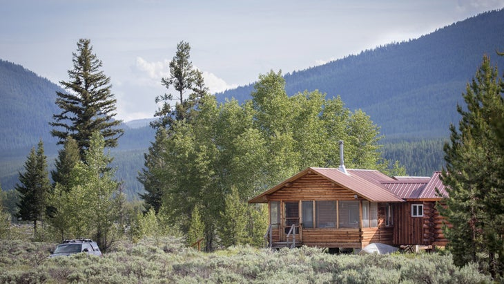 The cabin, with new additions, surrounded by regrowing forest and backed by the thickly forested Whitefish Range.