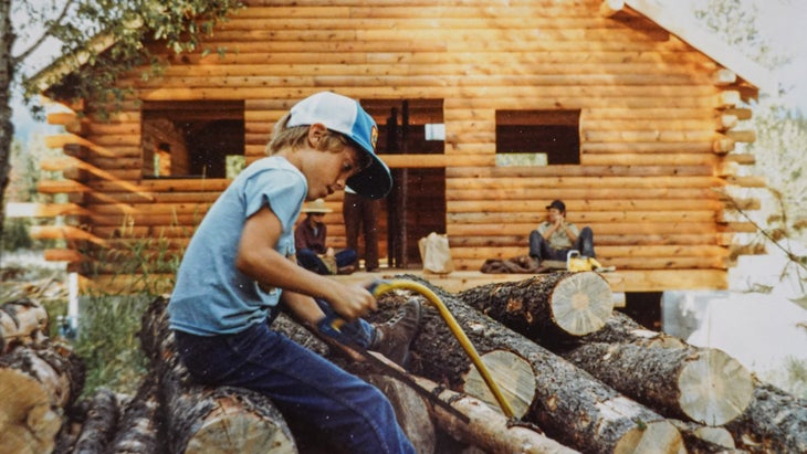 Young Aaron prepares logs for the next campfire while his grandfather's cabin is under construction.