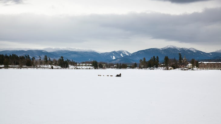 Dog sled in the distance on the frozen lake with mountains in the background. Lake Placid, NY