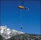 A park service chopper hoists a honey bucket out of the Tetons.