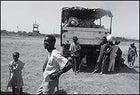 Refugees loiter around a supply truck.