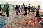 """""""In this sad life"""": Pentecostal worshipers dance on the beach south of Luanda after a funeral."""