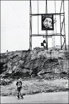 On the outskirts of Kabul, a boy waits beneath an image of the late Ahmed Shah Massoud.
