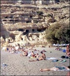 Sun worshippers lounge on Matala's protected beach, in front of caves used as ancient Roman tombs and Minoan storage cells.