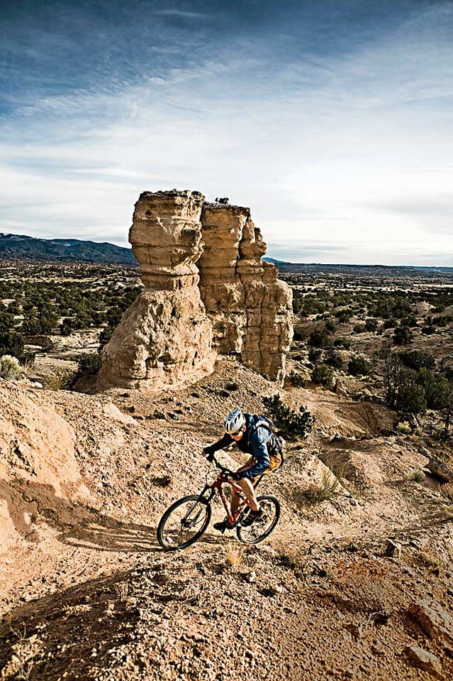 Achievement Arid Climate Awe Beauty In Nature Bicycle Bike Caucasian Appearance Challenge Color Image Copy Space Cycling Cyclist Day Determination Eroded Extreme Terrain Full Length High Angle View Landscape Leisure Activity Majestic Mountain Moving Up Natural Landmark Nature New Mexico One Person One Young Man Only Outdoors Photography Physical Geography Pojoaque Recreational Pursuit Rock Rock Formation Scenics Sports Clothing Sports Helmet Sports Training USA Vertical Vignette Young Adult