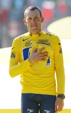 Lance Armstrong holds his hand on his chest as he listens to national anthems after winning his sixth straight Tour de France.