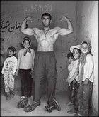 Iran with a human face: wrestler Parviz Kiai flexes for his fan club.