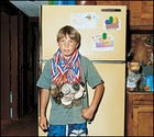 Lucky guy: Roger at home in Placerville, California, weighed down by 89 of his snowboarding medal