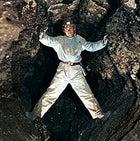 Ukrainian Speleological Association member Yevgeni Kislistim straddles a passage inside Ozernaja Cave, in Western Ukraine