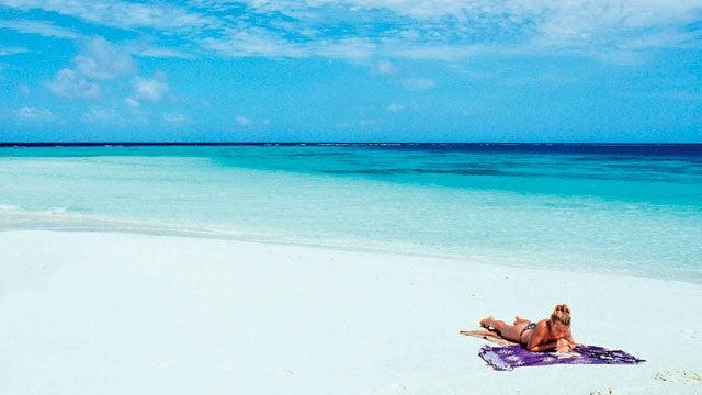 maldives island beach alone reading towel book island trips best travel