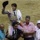 Frenchman Sebastian Castella waves to aficionados while riding triumphantly on the shoulders of a fellow bullfighter on the final day of Medellin's 2014 bullfighting season.