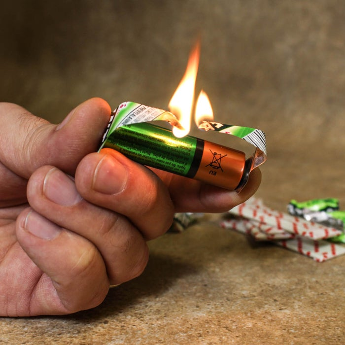In the middle of a catastrophe, that pack of Juicy Fruit serves a far greater purpose than just staving off hunger or freshening your breath. Use the foil-backed wrapper to short circuit an AA battery and create a flame. First, tear the wrapper into an hourglass shape and touch the foil to the positive and negative battery terminals. The electrical current will briefly cause the paper wrapper to ignite. Use the flame to light a candle or tinder.