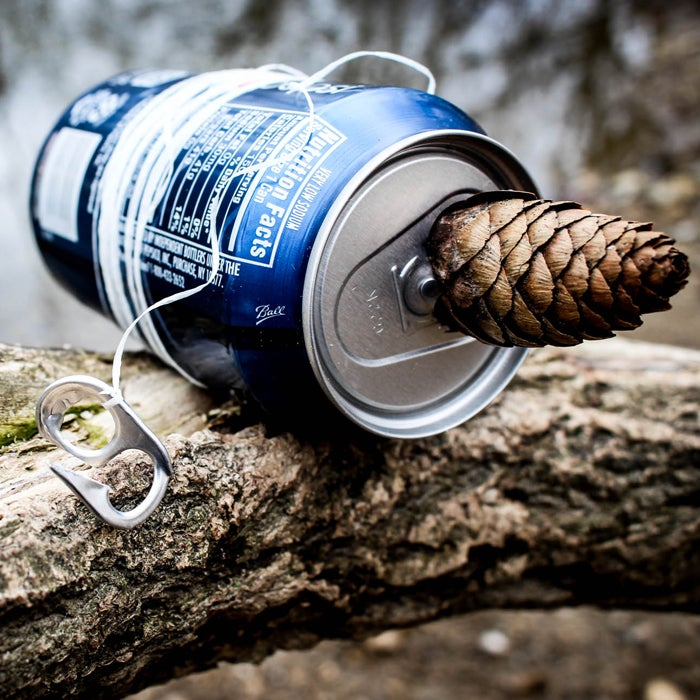 """When resources run low, use a tin pop can to make what is colloquially known as a """"hand-reel hobo kit""""—essentially an improvised fishing pole. Use a knife or pliers to pry off the tab on the top, and break apart one of the small rings into a barbed fishing hook. Tie it to a piece of dental floss or any other string-like material, and wind the rest around the can. Use the makeshift rod to catch perch or other small fish. You can even store worms for bait inside the empty can."""