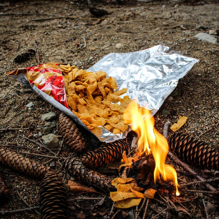 """When lost in the wilderness, food is a valuable commodity. However, under the right circumstances, a bag of oily chips might be better used as kindling for a signal fire than as a snack. """"A single bag can help get the flames roaring,"""" Stewart says, """"and as the smoke rises, use the shiny mylar interior of the bag to reflect sun as a beacon to rescue planes."""""""
