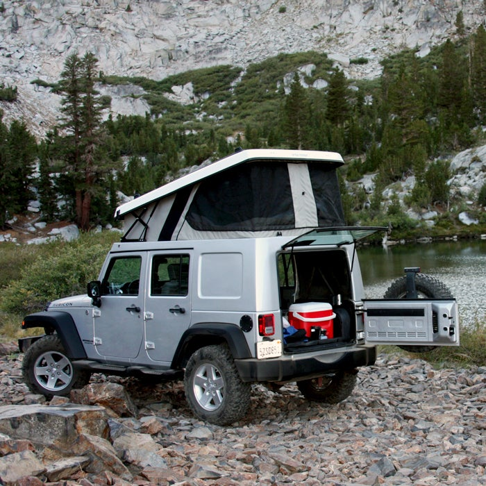 Ursa Minor gained fame with its E-camper Honda Element pop-up—a conversion that cost much less than other options on the market. When the car was discontinued, Ursa started making modern pop-tops for Jeep Wranglers (starting at $5,700).   The flatbed-camper design minimizes noise, maximizes fuel economy, and adds only about six inches to the Jeep's height. When fully opened, the space is large enough to accommodate a seven-foot mattress, interior LED lighting, and zippered screen windows. You'll be comfortable, no matter the campsite. A fold-over version holds four people.