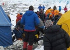 Ueli Steck (lower left) on the ground at Everest's Camp 2, after being attacked by Tashi Sherpa. Simone Moro can be seen fleeing camp (upper left, orange jacket).