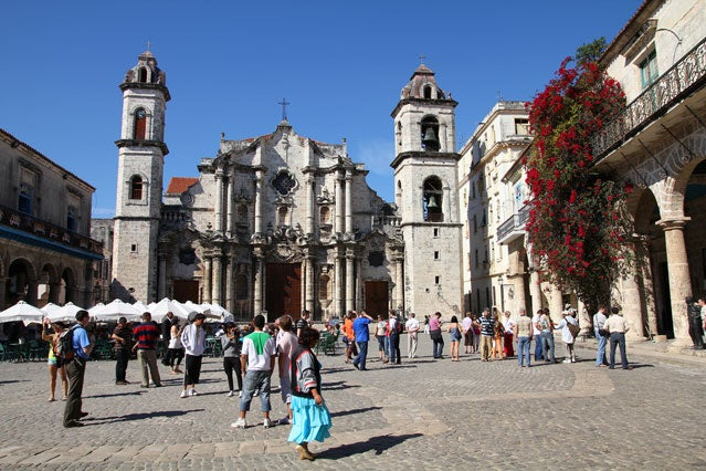 Tourists visit a cathedral in Havana.
