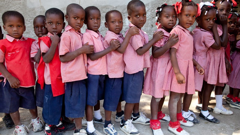 Children line up in front of their classroom before class at Church of God of Savanne Tapion School.