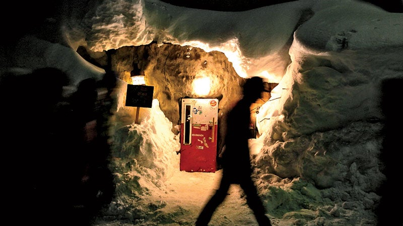 Gyu + bar in Niseko Hirafu area. The entrance of the bar is a small refrigerator. People have to lean front to enter the bar. The bar is packed by foreign tourists.