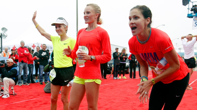 Joan Benoit Samuelson, Shalane Flanagan, and Kara Goucher cheer on other runners after completing the half marathon at the ninth annual Nike Women's Marathon in San Francisco.