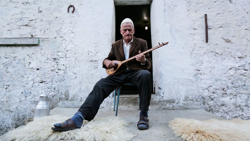 A villager in Thethi, Albania, strums a traditional, single-string lahuta. Albania is the only country along the Via Dinarica that was not a member of Yugoslavia.
