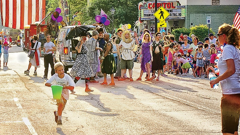 running Montpelier Mile July 4 footrace. in Montpelier Vermont joyful boy running towards mother spectators watching cast of Midsummer Night's Dream Shakespeare production by Lost Nation Theater American Flag State Street outside best towns ever