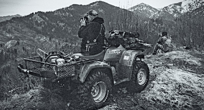 Wolf hunting guide Elijah Coley, left, scans terrain atop Granite Basin with Zeb Redden, right, during a wolf hunt in the Boise National Forest.
