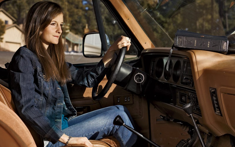 Alicia Shay, with her husband's bible on the dashboard, near her home in Flagstaff, Arizona. Click to enlarge.